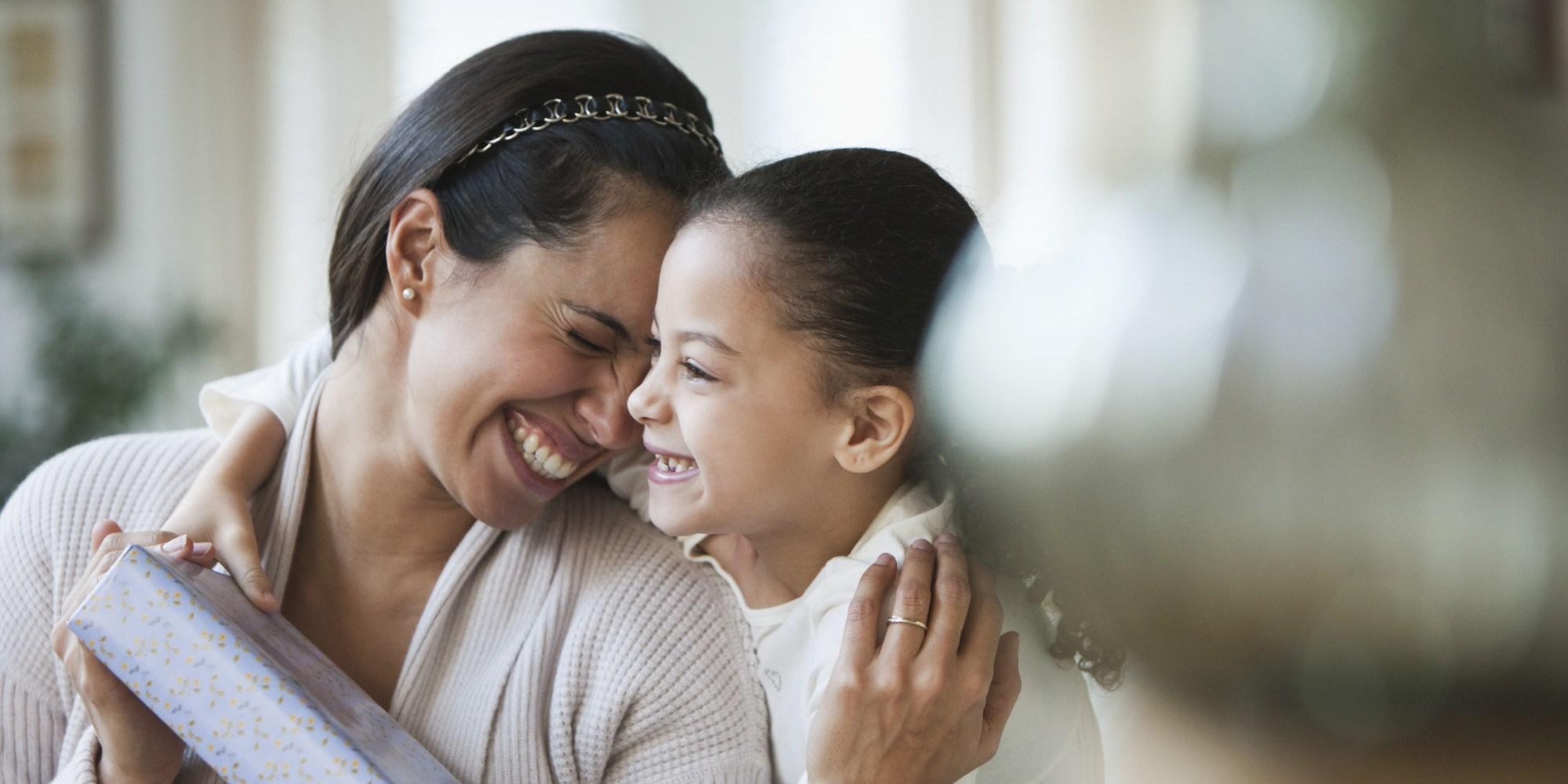 Hispanic girl giving mother birthday gift