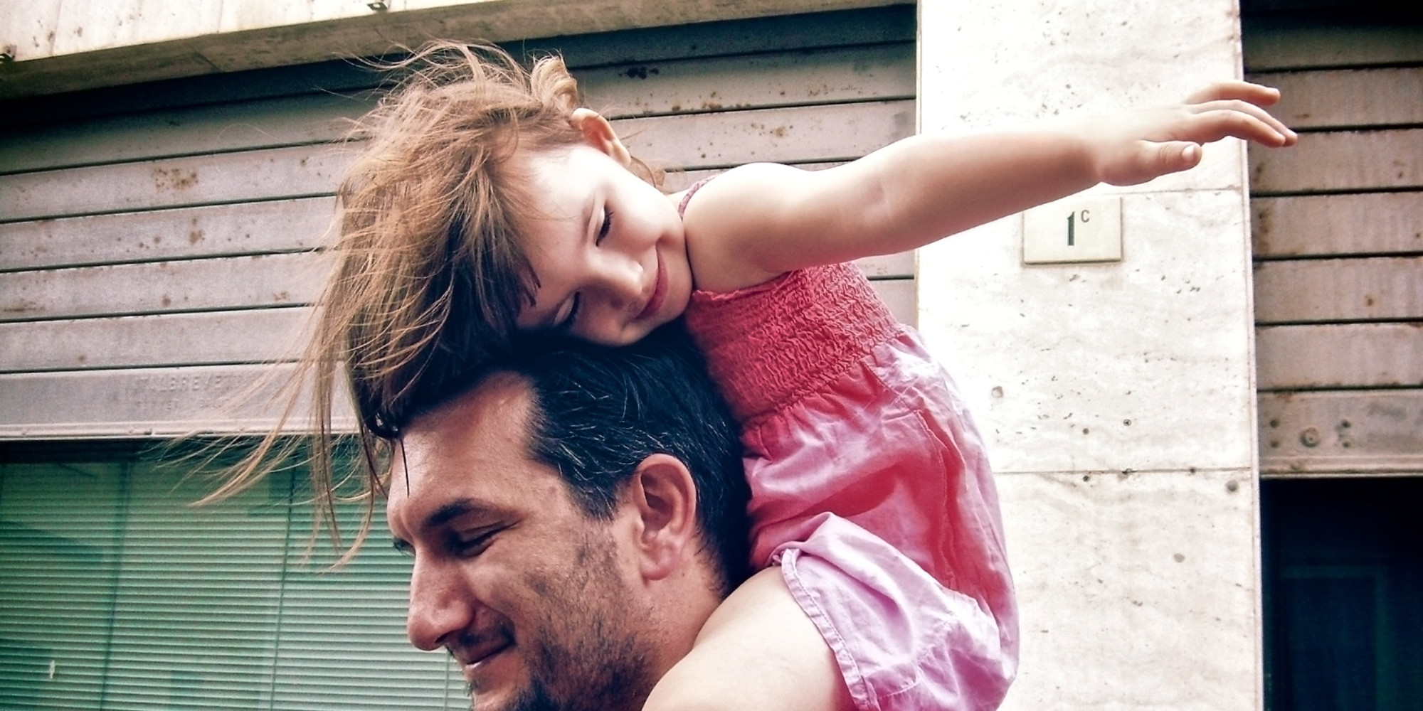 Little girl rides high on dad's shoulders
