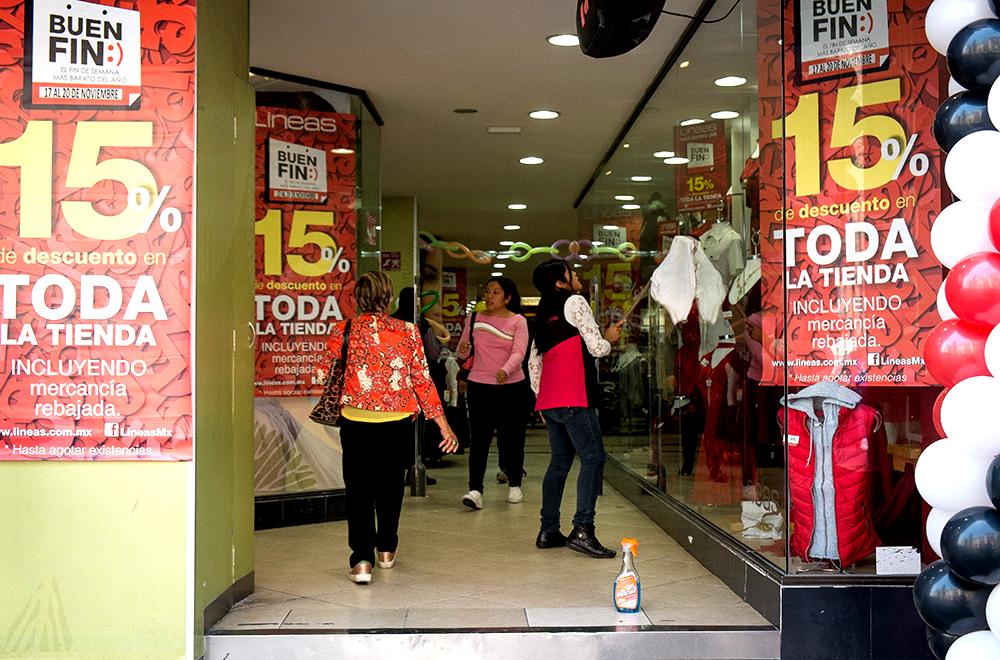 """CIUDAD DE MÉXICO, 17NOVIEMBRE2017.- Mujer limpia Vitrina con promocionales sobre el Buen fin. El séptimo """"Buen fin"""" se llevará a cabo del 17 al 20 de noviembre en todo el país, el servicio de Administración Tributaria (SAT) proyecta ventas por 100 mil millones de pesos, lo que representaría un incremento  de 12% respecto el año pasado según la INEGI. Aunque exista un incremento económico favorable, hay riesgos latentes en las dinámicas económicas; la más importante tendría que ver con el endeudamiento, la forma más riesgosa de endeudarse es utilizar créditos sin plazos fijos y que generan intereses. FOTO: ANDREA MURCIA /CUARTOSCURO.COM"""