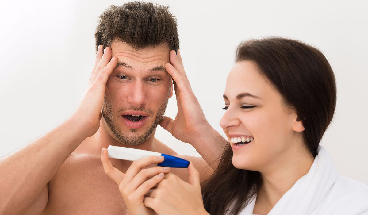 Portrait Of Young Couple Looking At Pregnancy Test Over White Background