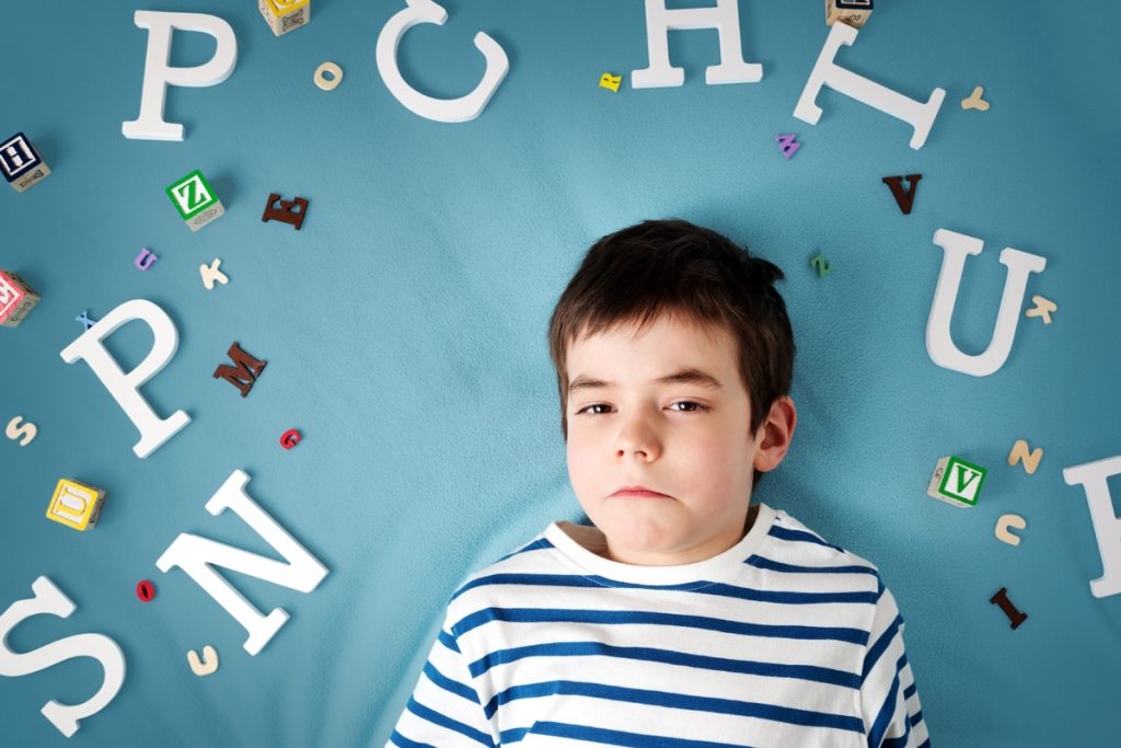 seven years old child lying with letters on blue background