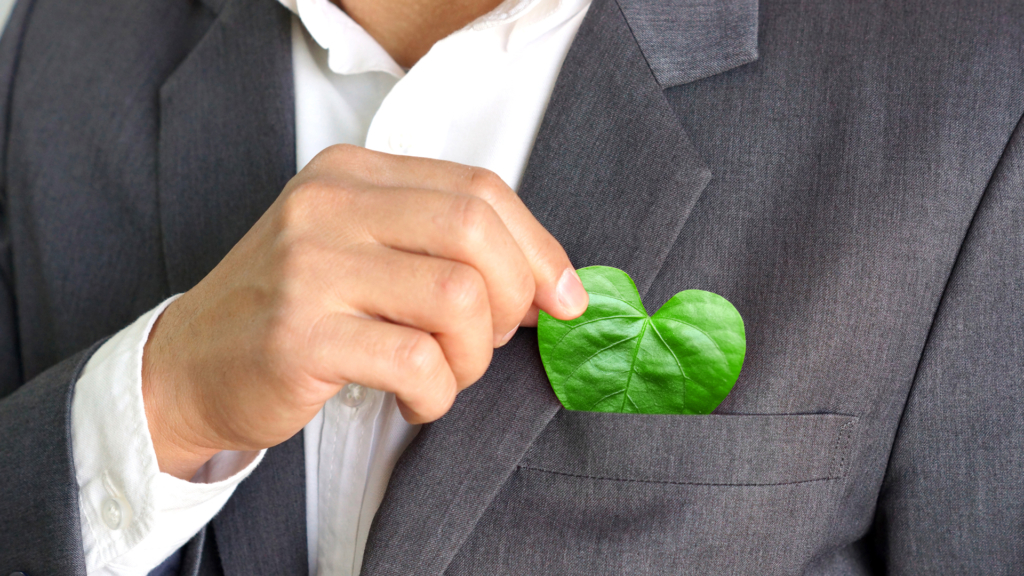 Businessman putting a green leaf with a heart shape from his pocket / Green business / Business with corporate social responsibility and environmental concern