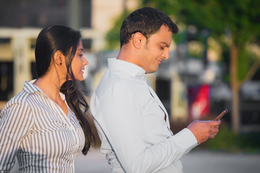 40923625 - closeup portrait, woman watching man over shoulder happily texting someone else, isolated outdoors background. negative emotion facial expression feelings conflict concept