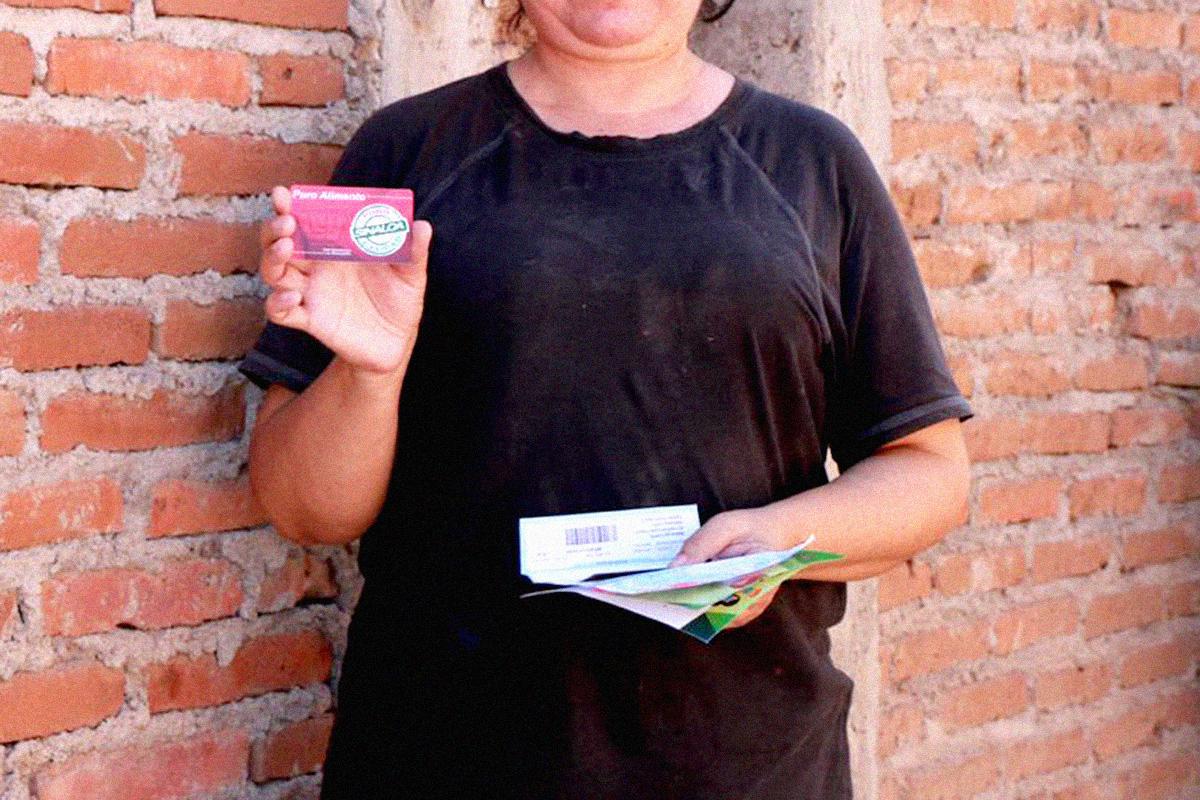 Mujer sostiene tarjeta de despensa durante el primer día de entrega de las mismas. FOTO: Cortesía/Sedeso.